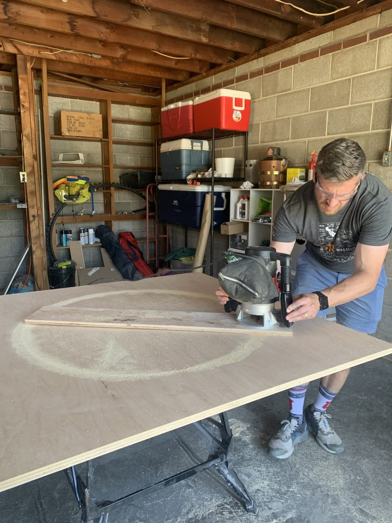 Brian from Dads by Design using router to cut maple plywood for modern DIY coffee table top