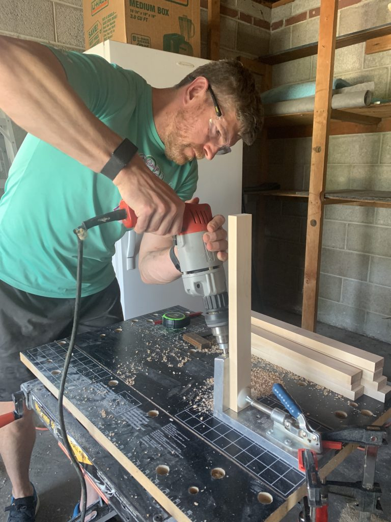 Brian from Dads by Design drilling pocket holes for DIY coffee table using Kreig Jig